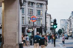 People walking on Oxford street near entrance to Oxford Circus tube station, London, UK royalty free stock photo