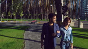 People walking in park enjoy stroll. Young family spend time at the open air sunny day autumnal day. Young woman and handsome man talking and discussing stock video footage