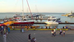 People walking in the parking lot of pleasure boats and yachts stock video footage