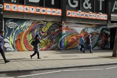 People walking past graffiti in Croydon,UK. People walking past two closed-down shops whose shutters are now covered with graffiti Stock Photos