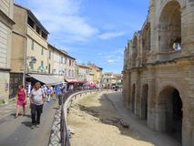 People walking past Roman amphitheatre. People walking past the Roman amphitheatre in the city of Arles in Provence, France Stock Images