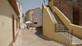 People walking past a small Portuguese alleyway. A wide still shot of people walking through an old and small Portuguese alleyway with buildings made from red stock video footage