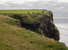 People walking on path along the Cliffs of Mohr Royalty Free Stock Photos
