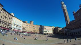 People walking in the Piazza del Campo, Siena, Italy. The square helds the Palazzo Pubblico and its Torre del Mangia and, twice a year, the famous horse race stock video