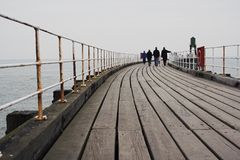 People walking on pier. Scenic view of curving wooden pier with people walking in background, Whitby, North Yorkshire, England Royalty Free Stock Images
