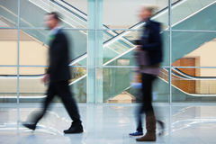 People Walking Quickly down Hall in Office Building. A people rushing through corridor Royalty Free Stock Photography