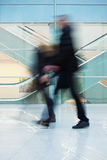 People Walking Quickly down Hall in Office Building. A people silhouettes in motion blur Royalty Free Stock Photo