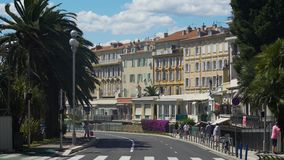 People walking quiet street with terraced buildings, sunny day in Nice, France. Stock footage stock footage
