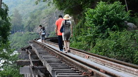 People walking on rail road. The railway line was built by the Empire of Japan in 1943 to support its forces Japanese into the Burma in World War II, at stock video