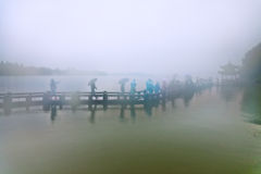People walking in the rain on the bridge Stock Photos