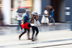 People walking in the rainy city Stock Photos