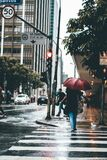 People walking on rainy city sidewalk Stock Photography