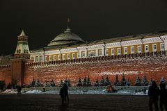 People walking on Red Square at night near Lenin`s Mausoleum in winter stock images