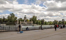 People walking in the Retiro park. Near the top blanket of Madrid with puerta de alcala in the background, is a sunny day. Picture taken in May 2014 Stock Photos