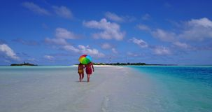 2 people walking romantic young people couple holding hands on a tropical island of white sand beach and blue. Two 2 people walking romantic young people couple stock video footage