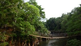 People walking on rope bridge cross over Tad Pha Suam waterfall in Pakse stock video footage