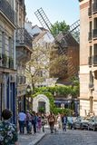 People walking in rue Lepic, view on the famous Moulin de Galette on the hill of Montmartre in Paris France. People walking in rue Lepic, view on the famous Stock Photos