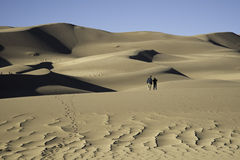 People walking on Sand Dunes. A couple walking on the Great Sand Dunes Royalty Free Stock Image