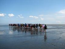 People walking into a sea Stock Photo