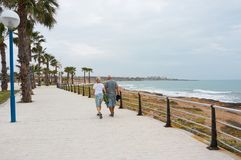 People walking by seafront stock images
