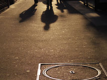 People walking shadow cast on street Royalty Free Stock Photos