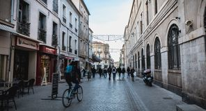 People walking in a shopping street in the historic city center of Sete, France. Sete, France - January 4, 2019: People walking in a shopping street in the royalty free stock image