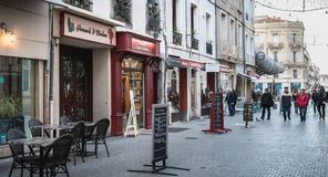 People walking in a shopping street in the historic city center of Sete, France. Sete, France - January 4, 2019: People walking in a shopping street in the royalty free stock images