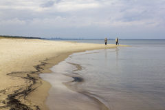 People walking the shore of the Baltic Sea, Poland. Two women walking along the Baltic coast royalty free stock photography