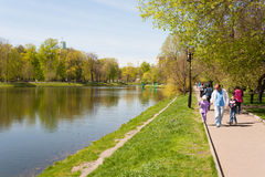 People walking on shore of pond in Catherine Park. MOSCOW - MAY 07: People walking on the shore of the pond in Catherine Park on May 7, 2015 in Moscow. Catherine stock photography