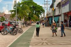 People walking on the sidewalk on Avenida Tulum. Tulum, Mexico - 7 August 2018: People walking on the sidewalk on Avenida Tulum stock photo