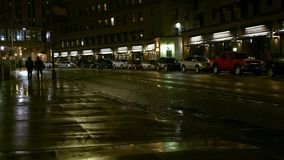 People walking on the sidewalk at night in urban rainy city. 