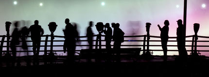 People walking silhouettes. Silhouettes of people walking along a fenced walkway at night stock photo