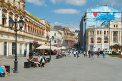 People walking and sitting on benches on Kuznetsky Most Street Stock Photos