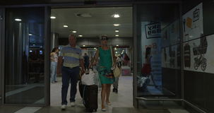 People Walking through the Sliding Doors in Airport. THESSALONIKI, GREECE - AUGUST 2, 2015: Travelling people are walking through the airport sliding doors, they stock video footage