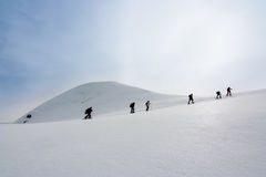 People walking with snow rackets towards the summit of a  hill. Line of people walking with snow rackets towards the summit of a snowy hill Royalty Free Stock Images