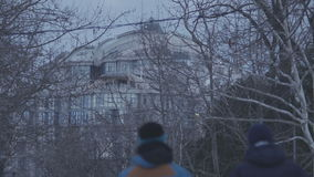 People walking on snowy road in front of the building in cold winter day stock footage