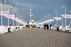 People walking on the Sopot Pier, Baltic Sea. SOPOT, POLAND, APRIL 26: Unidentified people walking on the Sopot Pier built in 1827. At 511m, the pier is the stock photography