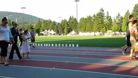 People walking on stadium race track with relay for life sepcial event in Coquitlam center park. stock footage