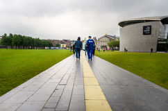 People Walking on a Stone Path. Amsterdam, The Netherlands - June 13, 2016: People walking on a paved path in Museum Square on a cloudy day. Three major Royalty Free Stock Photography