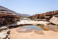 People walking on the stone river, Draa valley (Morocco) Royalty Free Stock Image