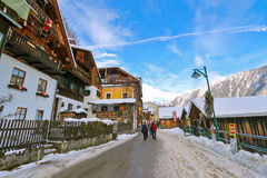 People walking on street covered with snow at Hallstatt, Austria. People walking on street covered with snow along Hallstaetter See, Hallstatt Lake in Upper stock image