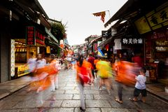People walking in street, dragging shutter royalty free stock photo