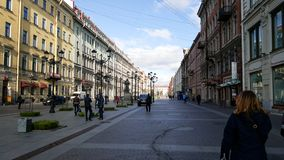 People walking on a street in St. Petersburg, Russia with buildings and lightposts clear day royalty free stock image