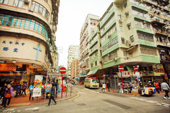 People walking on street with tall concrete buildings in Hong Kong. Stock Photography