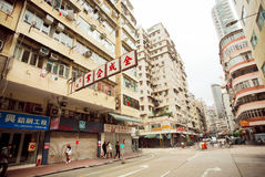 People walking on street with tall concrete buildings in Hong Kong. Stock Photo
