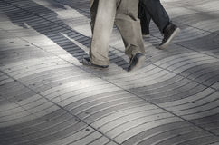People walking on street. People walk on Wave Patterns on a street in Barcelona stock photography
