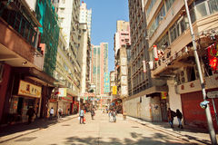 People walking on sunny street with tall concrete buildings in Hong Kong. Royalty Free Stock Image