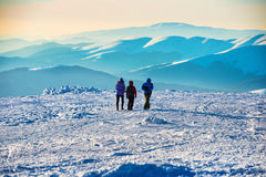 People walking at sunset in winter mountains Royalty Free Stock Photography