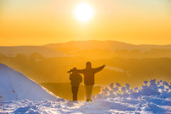 People walking at sunset in winter mountains Royalty Free Stock Photo
