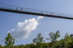 People walking on the suspension bridge over the trees in high h royalty free stock photos